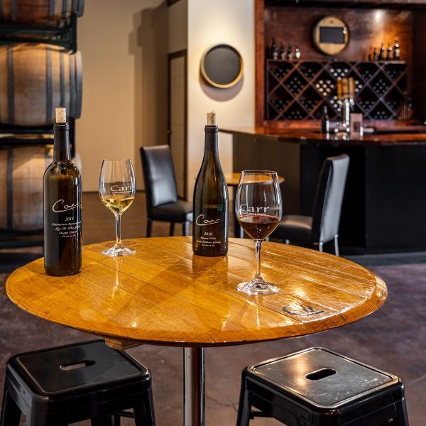 A cocktail table with wine glasses and bottles at Carr Winery in Santa Ynez