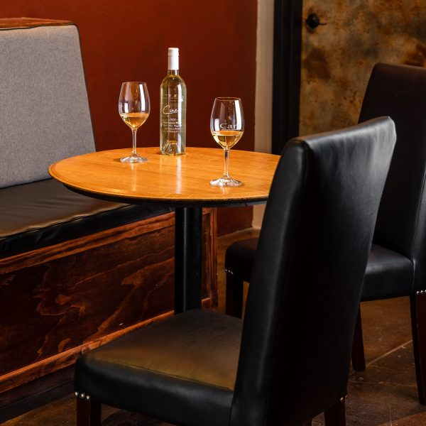 An inviting indoor barrel-top table with white wine glasses and bottle at Carr Winery in Santa Ynez